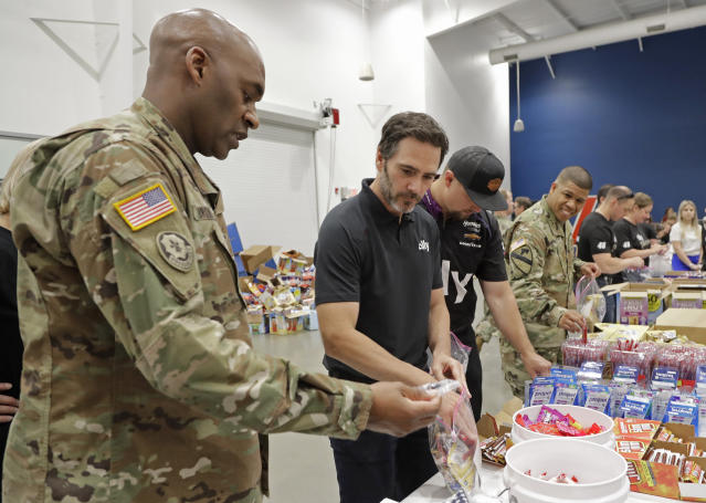 NASCAR driver Jimmie Johnson, second from left, helps assemble care packages for the North Carolina USO during a news conference in Concord, N.C., Tuesday, May 14, 2019. (AP Photo/Chuck Burton)