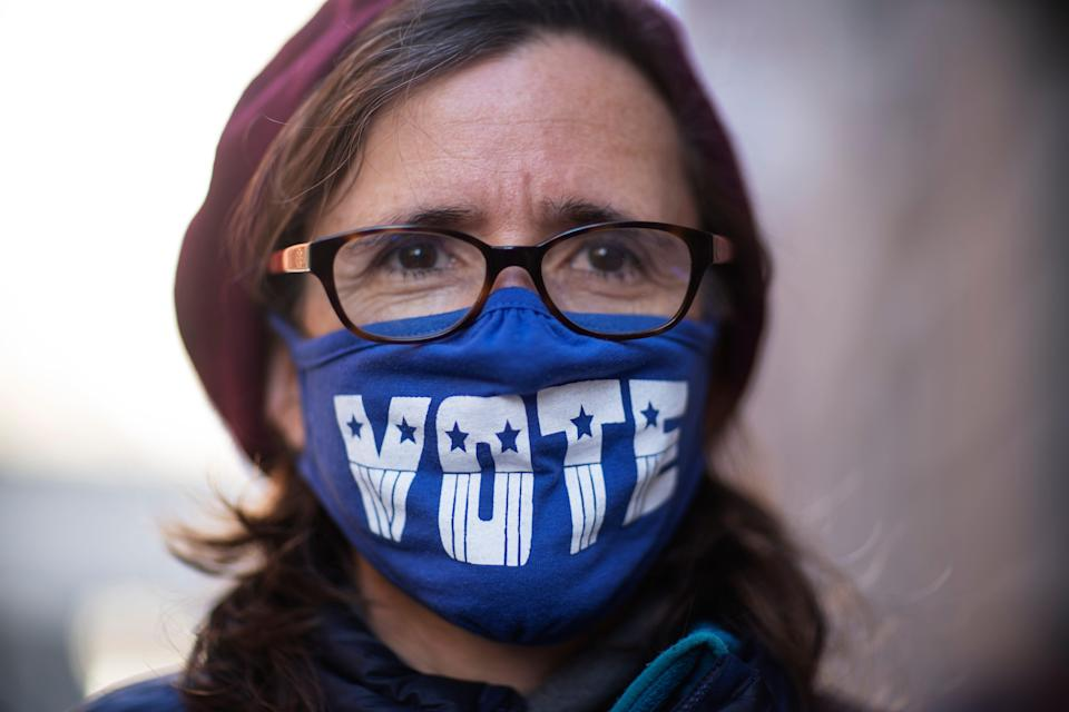 """Cathy Saunders wears a """"VOTE"""" mask while standing on line to cast her ballot in Providence, Rhode Island."""
