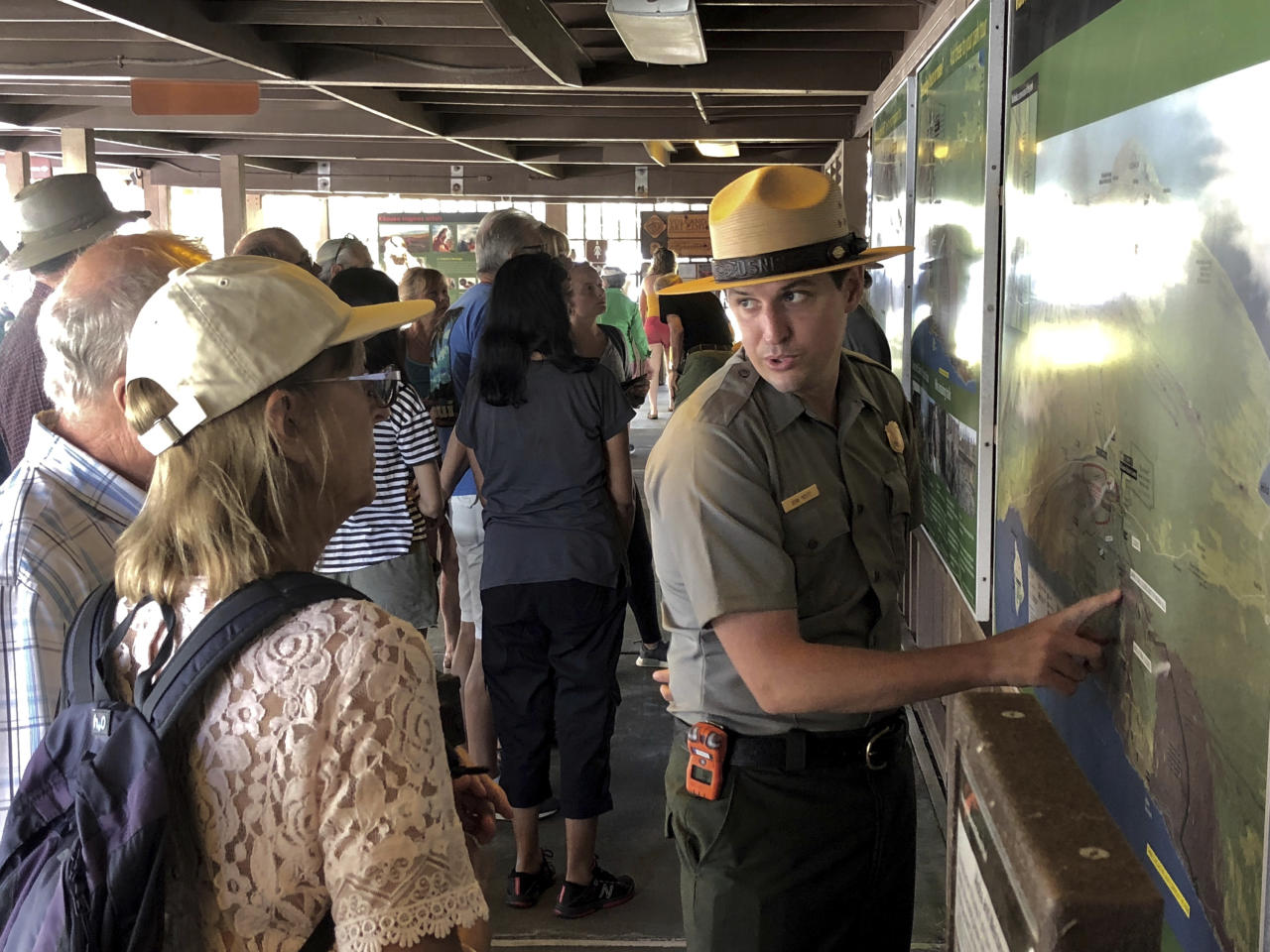 In this Saturday, Sept. 22,2018, photo released by the National Park Service shows tourists get directions on the first day Hawaii Volcanoes National Park is reopened after volcanic activity forced the park to close for more than four months in Hawaii. (Janice Wei/National Park Service via AP)