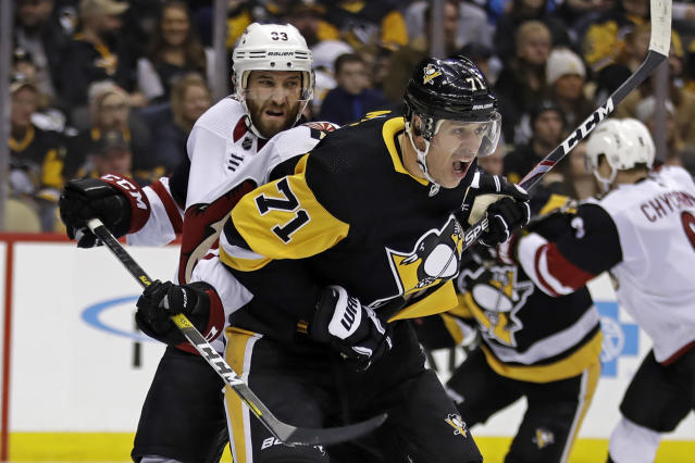 Pittsburgh Penguins' Evgeni Malkin (71) battles Arizona Coyotes' Alex Goligoski (33) for position in front of goalie Antti Raanta during the second period of an NHL hockey game in Pittsburgh, Friday, Dec. 6, 2019. (AP Photo/Gene J. Puskar)