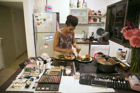 Karam Dadu, a transvestite homosexual Israeli Arab, prepares dinner before his drag show in Tel Aviv June 5, 2015. REUTERS/Baz Ratner