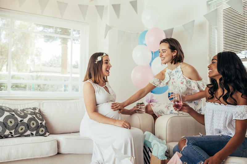 Three woman, one pregnant at a home baby shower