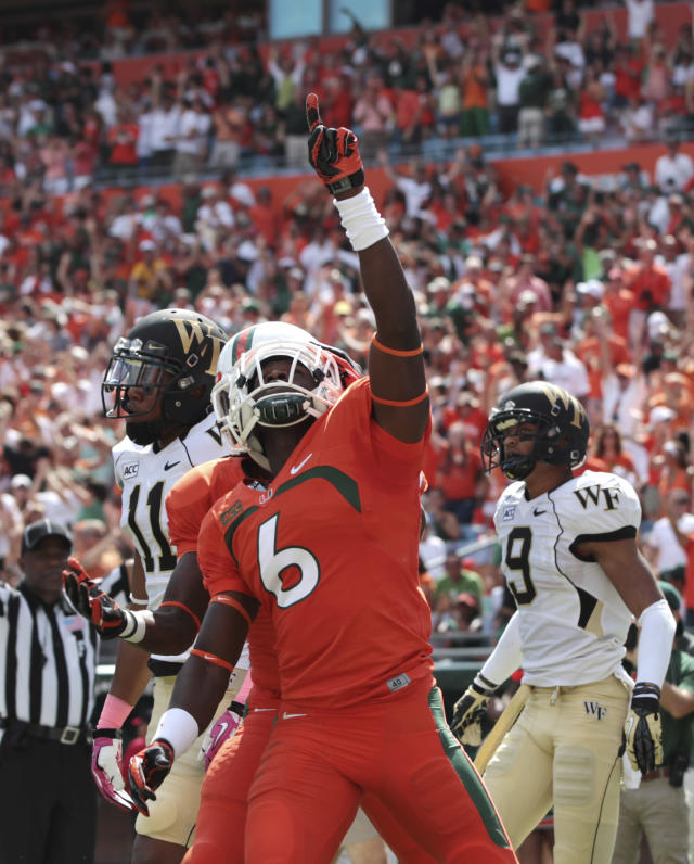 Miami's Herb Waters celebrates after scoring a touchdown during the first half of an NCAA college football game against Wake Forets in Miami Gardens, Fla., Saturday, Oct. 26, 2013. (AP Photo/J Pat Carter)