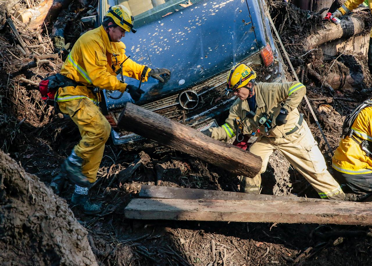 <p>Rescue workers scour through cars for missing persons after a mudslide in Montecito, Calif., Jan. 12, 2018. (Photo: Kyle Grillot/Reuters) </p>