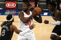 Julius Randle, center, of the New York Knicks looks to pass as Jarred Vanderbilt, left, and Anthony Edwards, right, of the Minnesota Timberwolves defend during the first half of an NBA basketball game Sunday, Feb. 21, 2021, in New York. (Sarah Stier/Pool Photo via AP)