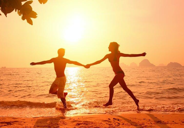 A couple running together on a beach at sunset