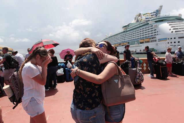 <p>Women hug as people line up to board a Royal Caribbean cruise ship that will take them to the U.S. mainland, in San Juan, Puerto Rico Sept. 28, 2017. (Photo: Alvin Baez/Reuters) </p>