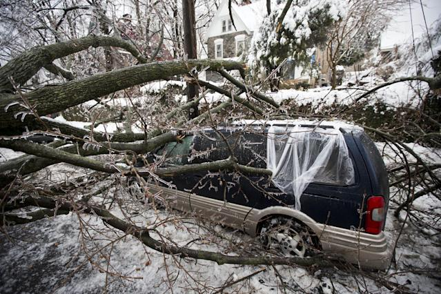 A downed tree covered in ice lays atop a minivan after a winter storm Wednesday, Feb. 5, 2014, in Philadelphia. Icy conditions have knocked out power to more than 200,000 electric customers in southeastern Pennsylvania and prompted school and legislative delays as well as speed reductions on major roadways. (AP Photo/Matt Rourke)