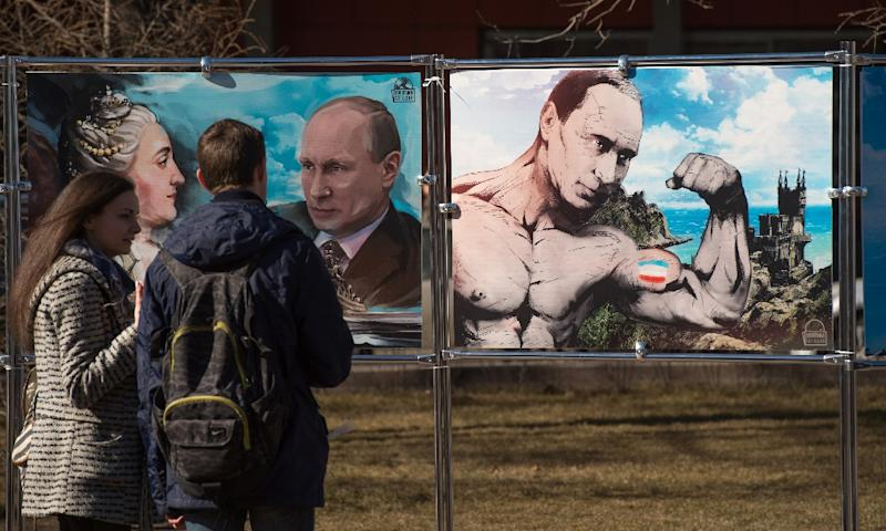 A couple stand close to pictures depicting Russia's President Vladimir Putin at a political cartoons exhibition in Moscow, on March 16, 2015 (AFP Photo/Dmitry Serebryakov)