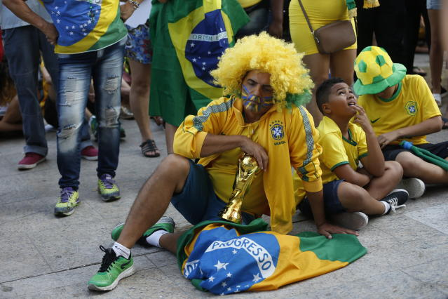 <p>Brazil soccer fans sit dejectedly on the ground as they watch a live telecast of the Brazil vs. Belgium World Cup quarter finals soccer match, in Rio de Janeiro, Brazil, Friday, July 6, 2018. (AP Photo/Silvia Izquierdo) </p>