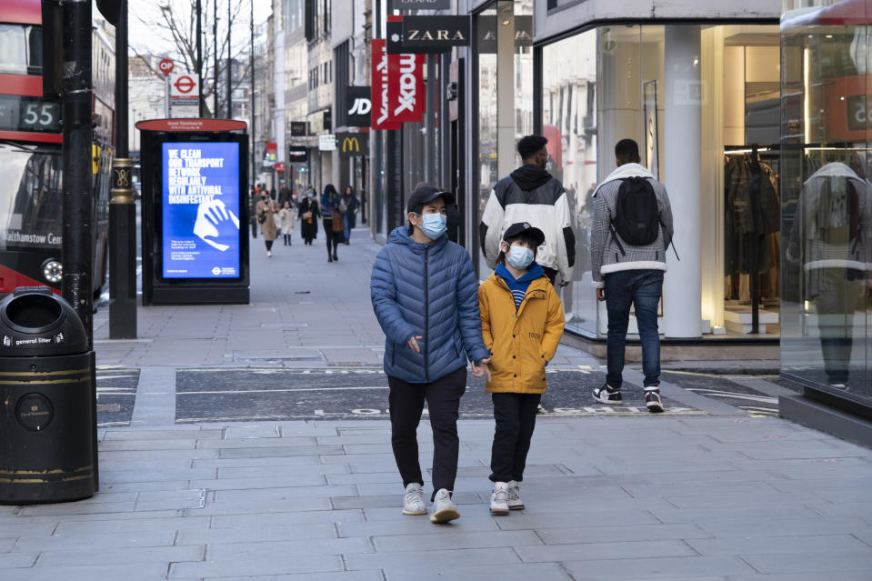 People wearing face masks walk along the shopping district Oxford Street which is largely empty of shoppers as the national coronavirus lockdown three continues on 28th January 2021 in London, United Kingdom. Following the surge in cases over the Winter including a new UK variant of Covid-19, this nationwide lockdown advises all citizens to follow the message to stay at home, protect the NHS and save lives. (photo by Mike Kemp/In Pictures via Getty Images)