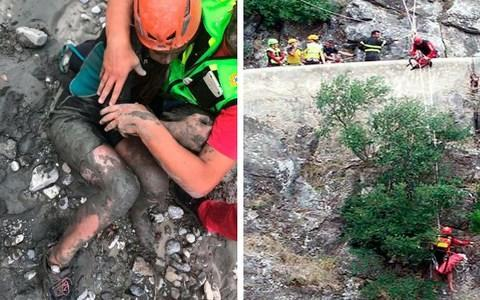 <span>A girl is helped by a member of the National Alpine and Caving Rescue Squad as they (right) descend the gorge</span> <span>Credit: ANSA/AP </span>