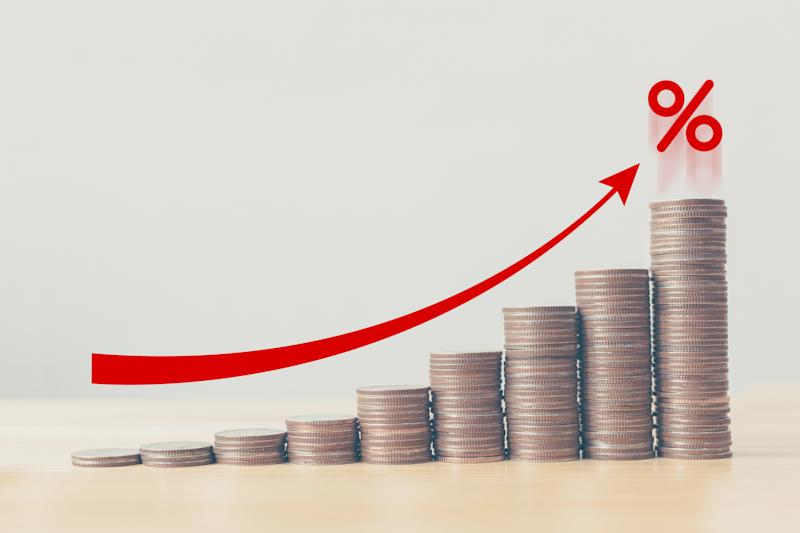 Rising stacks of coins with a red arrow pointing to a percent sign.