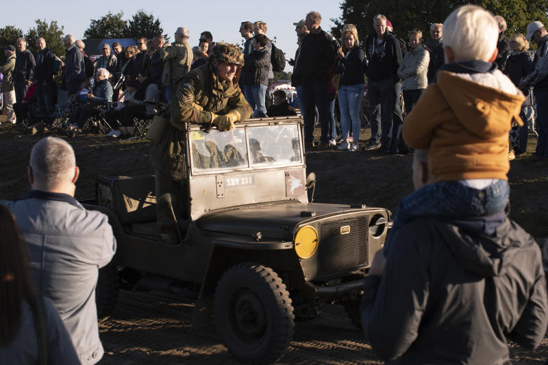 Spectators watch a parade of historic WWII military vehicles prior to a mass parachute drop at Ginkel Heath, eastern Netherlands, Saturday, Sept. 21, 2019, as part of commemorations marking the 75th anniversary of Operation Market Garden, an ultimately unsuccessful airborne and land offensive that Allied leaders hoped would bring a swift end to World War II by capturing key Dutch bridges and opening a path to Berlin. (AP Photo/Peter Dejong)