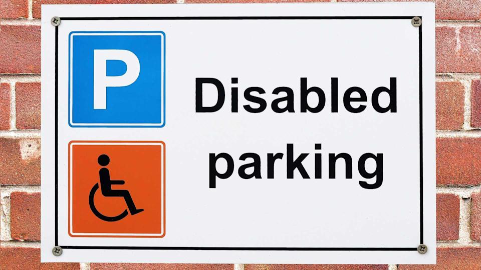 Disabled parking sign with parking and wheelchair symbols on brick wall