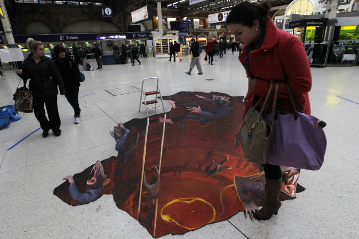 """A commuter checks her step as she walks past a 3D art exhibit """"Escape the Rat Race' painted on the concourse of Victoria railway station in London to promote a pest control company, Wednesday, Jan. 18, 2012. (AP Photo/Sang Tan)"""