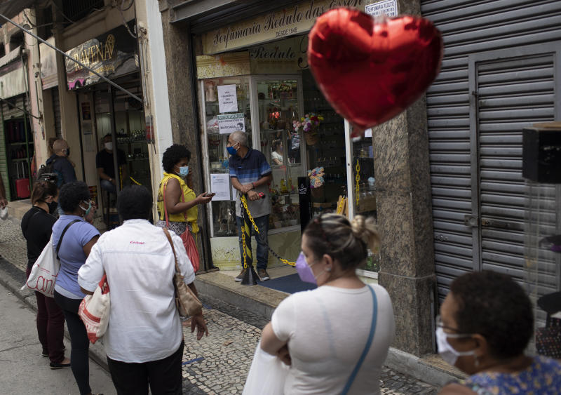 People wearing masks to curb the spread of the new coronavirus line up to get their temperatures checked before entering a store in downtown Rio de Janeiro, Brazil, Monday, June 29, 2020. This weekend Rio authorities allowed commerce and beauty salons to open their doors to the public as the city eases its lockdown amid the growing pandemic. (AP Photo/Silvia Izquierdo)