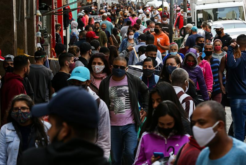 SAO PAULO, BRAZIL - JUNE 29: Shoppers wearing face masks walk in a crowded street in downtown amidst the coronavirus (COVID-19) pandemic on June 29, 2020 in Sao Paulo, Brazil. The city of Sao Paulo moves to the Yellow phase of quarantine easing, in which commercial establishments can operate following distance rules such as reduced opening hours, restricting the flow of people and maintaining hygiene standards. (Photo by Alexandre Schneider/Getty Images)