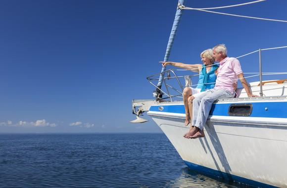A senior man and woman sit on a sailboat that's on the water.