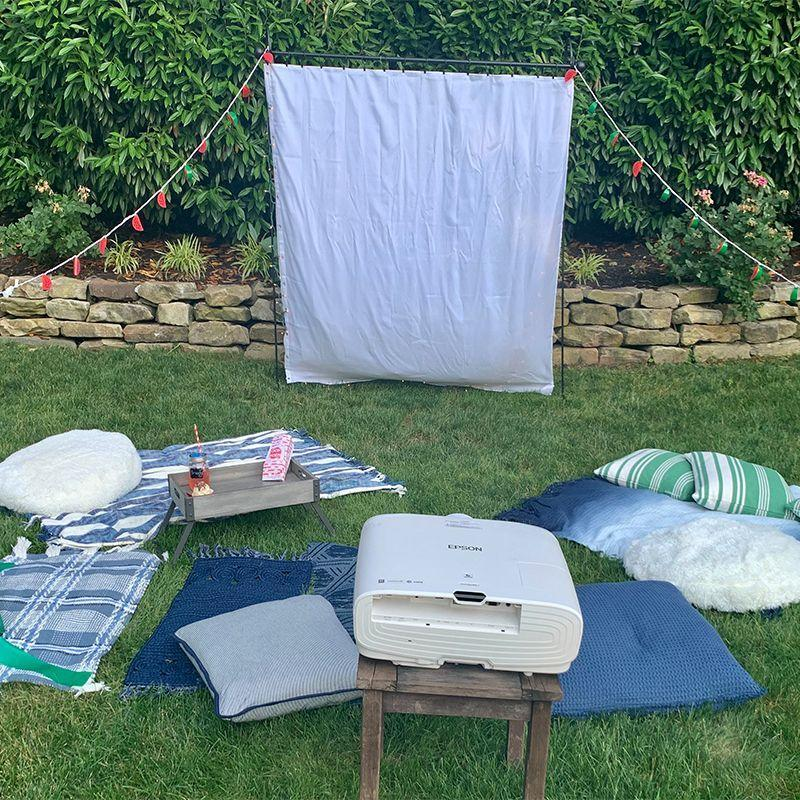 """<p>The projector will probably be the most expensive item to buy for your outdoor movie night, but it's well worth the investment. Pro tip: Invest in one with your friend group that you can pass around whenever one of you is having a movie night.</p><p>You can create a screen yourself using a weighted shower curtain or sheet, or you can buy one for as little as $30 online, so the choice is yours. <em>HGTV </em>suggests you use <a href=""""https://www.youtube.com/watch?v=EOmjTGpgOfo"""" rel=""""nofollow noopener"""" target=""""_blank"""" data-ylk=""""slk:hanging plant stands to secure your screen"""" class=""""link rapid-noclick-resp"""">hanging plant stands to secure your screen</a> so that it won't fall or blow away should the weather be tricky. </p><p><strong>What You'll Need: </strong><a href=""""https://www.amazon.com/KODAK-Luma-Pocket-Projector-Built/dp/B07RLXZ88F?tag=syn-yahoo-20&ascsubtag=%5Bartid%7C10070.g.33216073%5Bsrc%7Cyahoo-us"""" rel=""""nofollow noopener"""" target=""""_blank"""" data-ylk=""""slk:Projector"""" class=""""link rapid-noclick-resp"""">Projector </a>($220, Amazon); <a href=""""https://www.amazon.com/EurCross-Curtain-Water-Repellent-Weighted-Bathroom/dp/B07W5CSBV7/ref=sr_1_8?dchild=1&keywords=weighted+shower+curtain+liner&qid=1594068694&refinements=p_n_srvg_2947266011%3A3254100011&rnid=2947266011&sr=8-8&tag=syn-yahoo-20&ascsubtag=%5Bartid%7C10070.g.33216073%5Bsrc%7Cyahoo-us"""" rel=""""nofollow noopener"""" target=""""_blank"""" data-ylk=""""slk:weighted shower curtain liner"""" class=""""link rapid-noclick-resp"""">weighted shower curtain liner</a> ($18, Amazon); <a href=""""https://www.amazon.com/Shepherds-Resistant-Weddings-Hanging-Lanterns/dp/B016PTLVSE/ref=sr_1_5?dchild=1&keywords=hanging+plant+stands&qid=1594068775&sr=8-5&tag=syn-yahoo-20&ascsubtag=%5Bartid%7C10070.g.33216073%5Bsrc%7Cyahoo-us"""" rel=""""nofollow noopener"""" target=""""_blank"""" data-ylk=""""slk:hanging plant stands"""" class=""""link rapid-noclick-resp"""">hanging plant stands </a>($32 for 2, Amazon); curtain rod ($17, Amazon)</p>"""