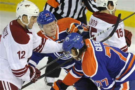 Edmonton Oilers' Tom Gilbert (77) defends against Phoenix Coyotes' Paul Bissonnette (12) as teammate Lennart Petrell, center, recoils after hitting Coyotes' Boyd Gordon, right, during the first period of an NHL hockey game in Edmonton, Alberta, on Saturday, Feb. 25, 2012. (AP Photo/The Canadian Press, John Ulan)