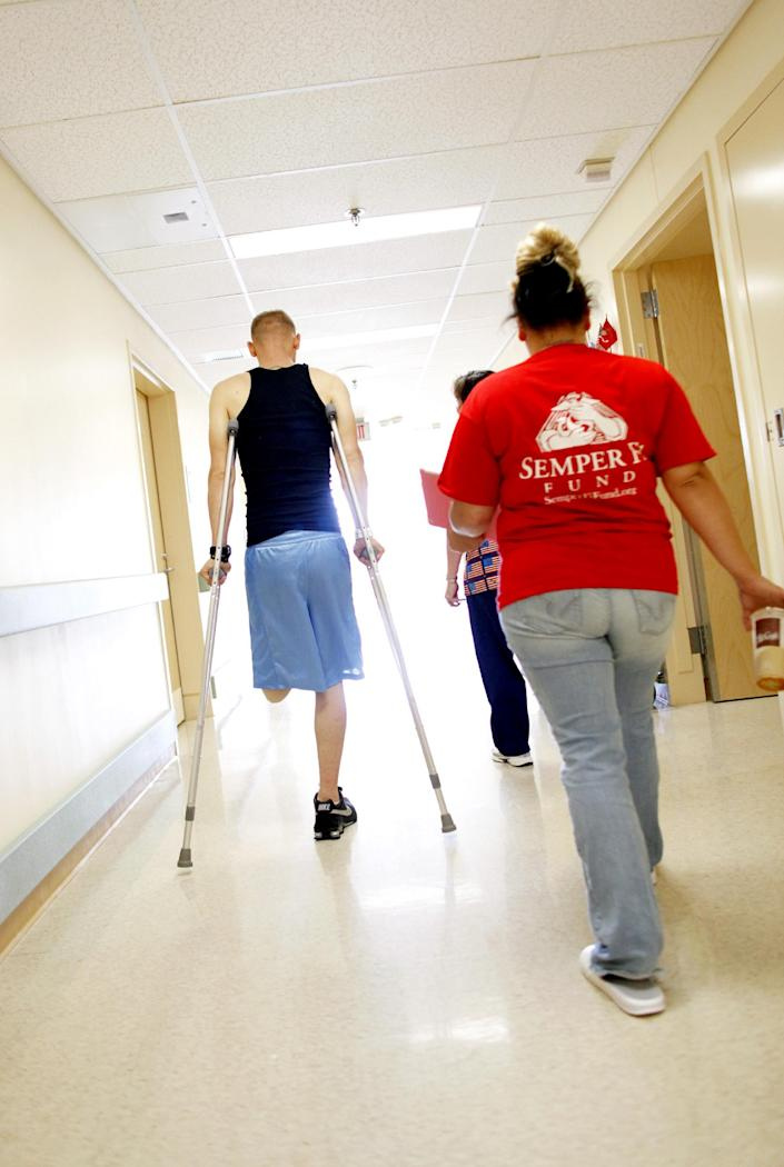 FILE - In this Tuesday, Aug. 2, 2011 file photo, Stephanie Childers, right, follows behind as her husband, Marine Lance Cpl. Caleb Childers, makes his way back to his room at the McGuire Veterans Affairs Medical Center in Richmond, Va. Childers, 20, was injured when he stepped on an IED in Afghanistan while on patrol June 30, 2011. A record number of new veterans from Iraq and Afghanistan are seeking compensation for service-related disabilities. So far, 45 percent have filed claims, more than double the 21 percent that did after some other recent wars. (AP Photo/Richmond Times Dispatch, Eva Russo, File)