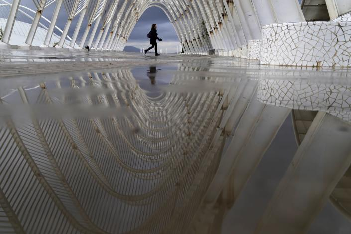 """A woman is reflected on rain water as she walks inside the modern Agora walkway at the main Olympic complex in Athens, Thursday, Oct. 14, 2021. Greece's authorities are in full activation mode as the wet and stormy weather system named """"Ballos"""" reached the country bringing thunder, lightning and showers, and causing fluctuations in the power supply. (AP Photo/Thanassis Stavrakis)"""