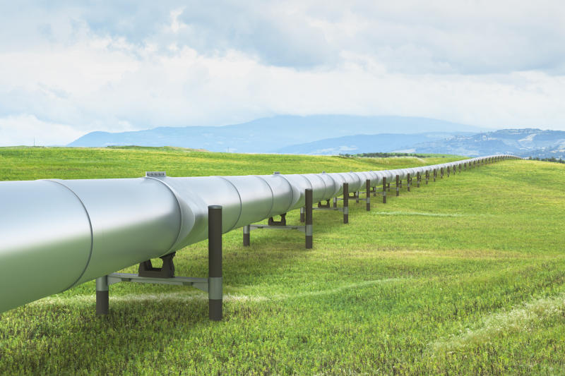 A pipeline in a green field heading off to the mountains.