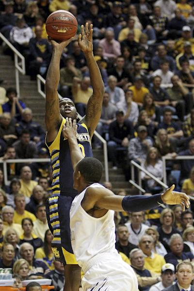 Marquette's Jamil Wilson, top, shoots over West Virginia's Keaton Miles in the first half of an NCAA college basketball game, Friday, Feb. 24, 2012, in Morgantown, W.Va. (AP Photo/David Smith)