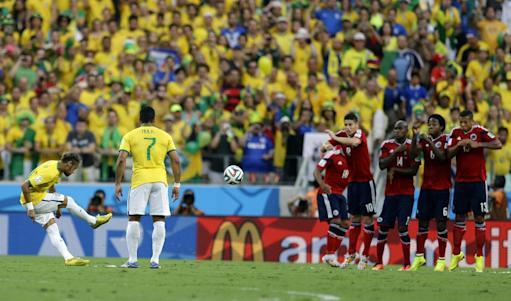 Brazil's Neymar takes a free kick against Colombia's defensive wall during the World Cup quarterfinal soccer match between Brazil and Colombia at the Arena Castelao in Fortaleza, Brazil, Friday, July 4, 2014. (AP Photo/Natacha Pisarenko)