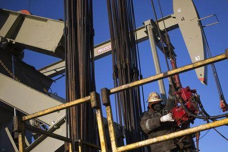 A man works on the rig of an oil drilling pump site in McKenzie County outside of Williston