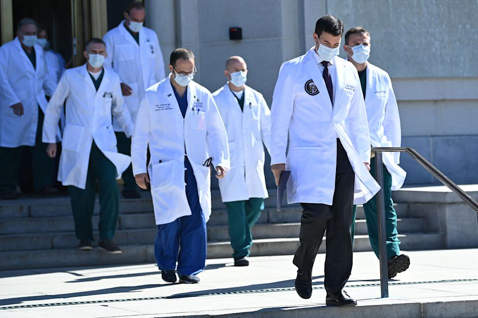 White House physician Sean Conley (2nd R), with medical staff, arrives to give an update on the condition of US President Donald Trump, on October 3, 2020, at Walter Reed Medical Center in Bethesda, Maryland. - Trump was hospitalized on October 2 due to a Covid-19 diagnosis. (Photo by Brendan SMIALOWSKI / AFP) (Photo by BRENDAN SMIALOWSKI/AFP via Getty Images)
