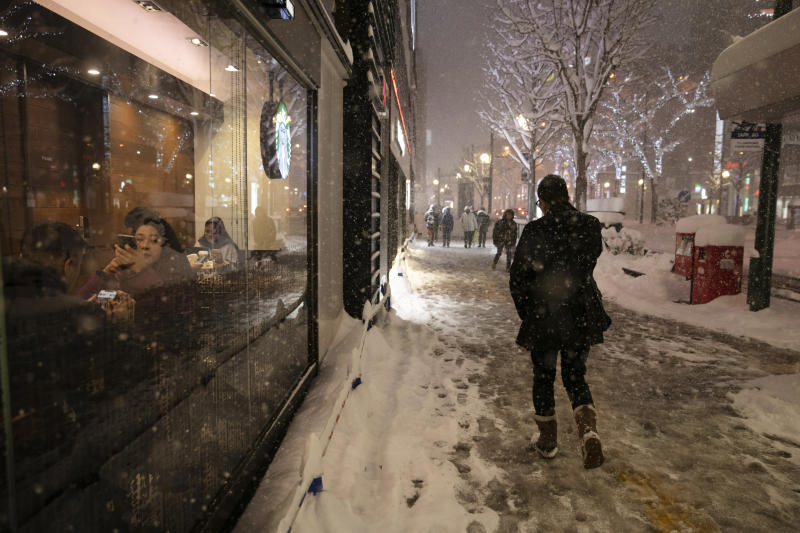 A man walks through a snow storm past a coffee shop Feb. 5, 2020, in Sapporo, Hokkaido, Japan. (AP Photo/Jae C. Hong)