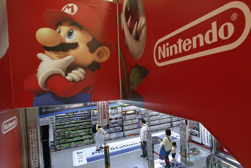 Shoppers walk under the logo of Nintendo and Super Mario characters at an electronics store in Tokyo Wednesday, May 7, 2014. Nintendo Co. sank to a loss for the fiscal year ended March as sales of its Wii U game machine continued to lag, but the Japanese manufacturer of Pokemon and Super Mario games promised Wednesday to return to profit this year. (AP Photo/Shizuo Kambayashi)