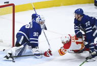 Toronto Maple Leafs goaltender Michael Hutchinson (30) makes a save against Calgary Flames left wing Milan Lucic (17) as Maple Leafs center Travis Boyd (72) gets a penalty on the play during second-period NHL hockey game action in Toronto, Monday, Feb. 22, 2021. (Nathan Denette/The Canadian Press via AP)