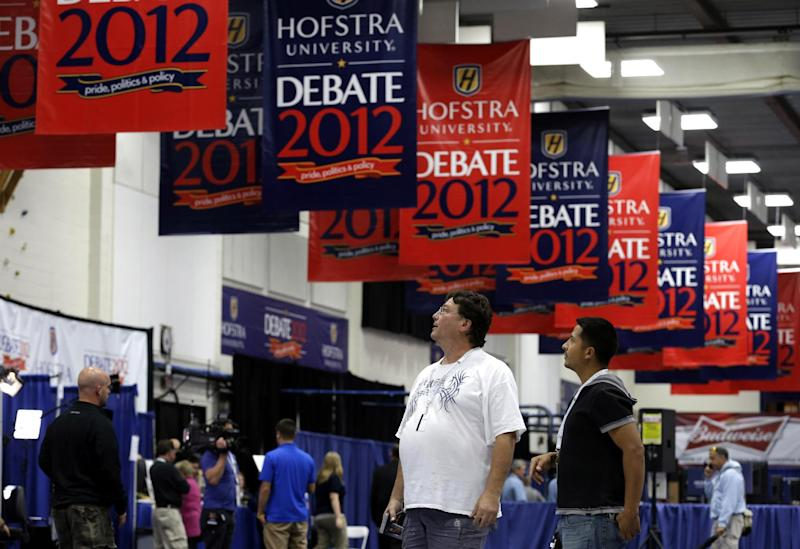 Billy Koske, left, and Jose Reyes look at signs hanging in the media filing center before Tuesday's presidential debate between President Barack Obama and Republican presidential candidate, former Massachusetts Gov. Mitt Romney, Monday, Oct. 15, 2012, at Hofstra University in Hempstead, N.Y. (AP Photo/Charlie Neibergall)