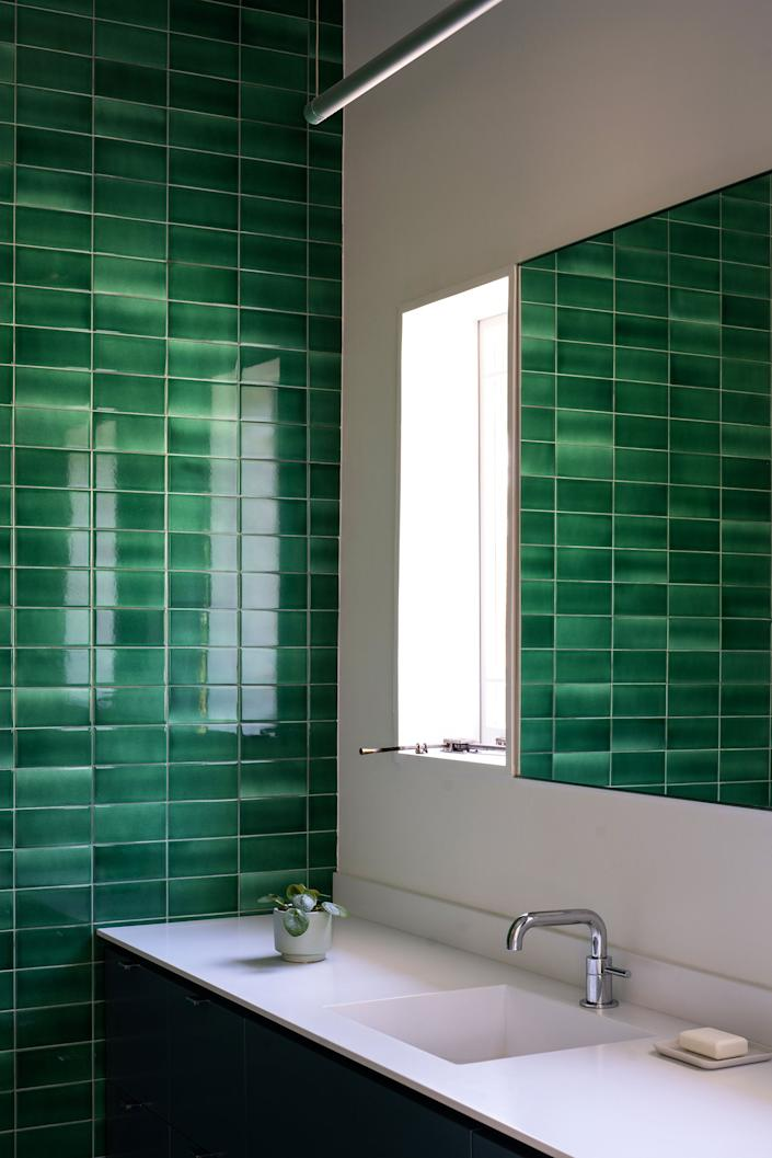 "<div class=""caption""> In the bathrooms, the team combined hexagonal tile to reference the home's original finishes with pops of color to signal the modern interventions. The <a href=""https://www.redrocktileworks.com/handmade-tile-glazes"" rel=""nofollow noopener"" target=""_blank"" data-ylk=""slk:glazed emerald tiles"" class=""link rapid-noclick-resp"">glazed emerald tiles</a> are from Red Rock Tileworks, and the Designer White Corian countertops are the same as in the kitchen. </div>"