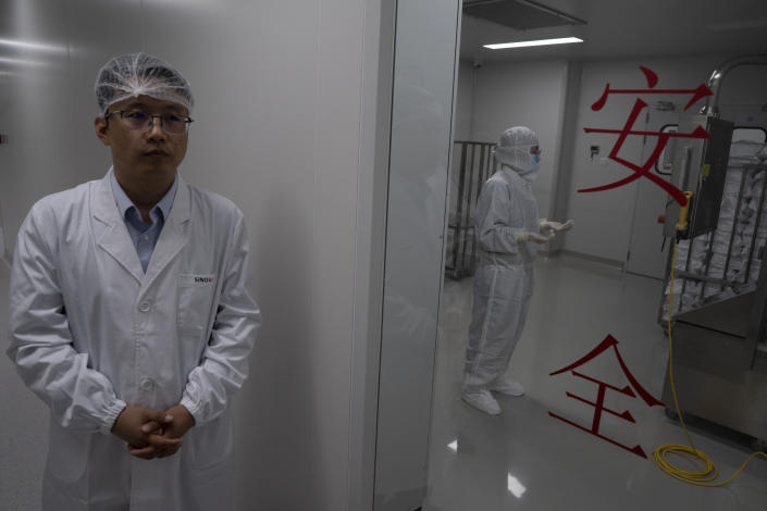 """A person works behind a glass door with the words """"Safety"""" at the SinoVac vaccine factory in Beijing on Thursday, Sept. 24, 2020. SinoVac, one of China's pharmaceutical companies behind a leading COVID-19 vaccine candidate says its vaccine will be ready by early 2021 for distribution worldwide, including the U.S. (AP Photo/Ng Han Guan)"""