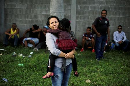 A Honduran woman carries her daughter as they wait to leave with a new caravan of migrants, set to head to the United States, at a bus station in San Pedro Sula, Honduras, January 14, 2019. REUTERS/Jorge Cabrera