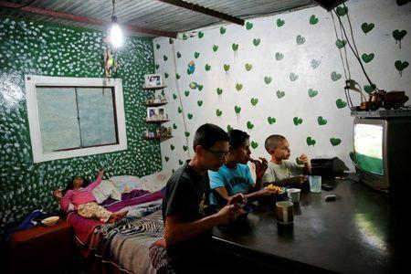 Doris Arocha (C), 30, who was sterilized two months ago, watches television with her children while they eat dinner at their home in San Diego, Venezuela July 19, 2016. REUTERS/Carlos Garcia Rawlins