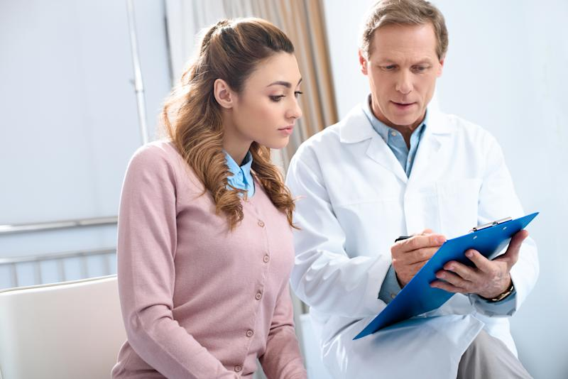 Doctor reviewing information on clipboard with female patient.