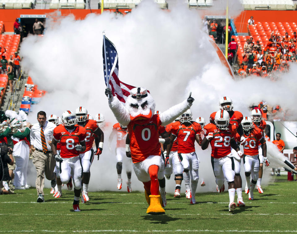 FILE - In this Sept. 29, 2012, file photo, University of Miami's mascot Sebastian the Ibis leads players onto the field before a NCAA college football game against North Carolina State in Miami. Miami's three-year NCAA probation largely stemming from the actions of rogue and now-former booster Nevin Shapiro gets completed on Friday, Oct. 21, 2016. It satisfies one of the most damning sanctions the Hurricanes were issued, though some aftereffects - scholarship reductions in football and men's basketball, most notably - will remain felt for a few more months. (AP Photo/J Pat Carter, File)