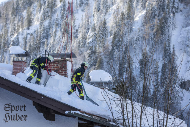 Firefighters clear the snow from a roof in Bayrischzell, Germany, Wednesday, Jan. 16, 2019. (Christoph Reichwein/dpa via AP)