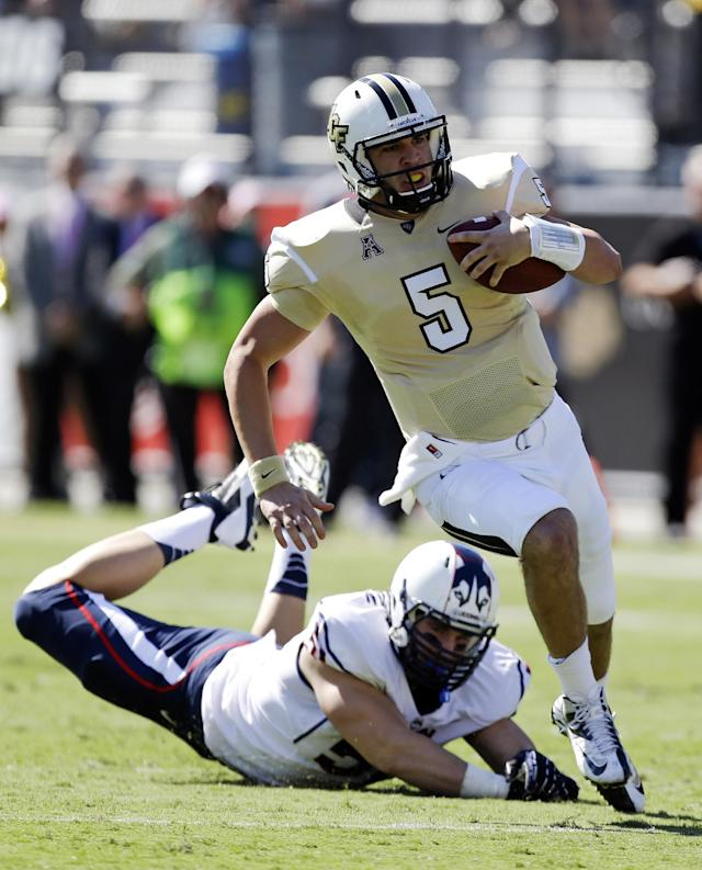 Central Florida quarterback Blake Bortles (5) runs past Connecticut defensive end Tim Willman, left, for a 16-yard gain during the first half of an NCAA college football game in Orlando, Fla., Saturday, Oct. 26, 2013.(AP Photo/John Raoux)