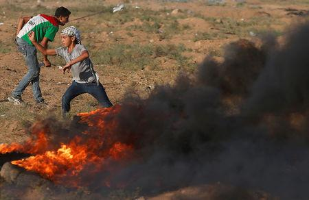 A Palestinian boy hurls stones at Israeli troops during a protest calling for lifting the Israeli blockade on Gaza and demanding the right to return to their homeland, at the Israel-Gaza border fence, east of Gaza City September 14, 2018. REUTERS/Mohammed Salem