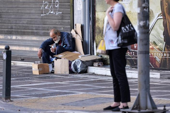 A homeless man sits while eating on the sidewalk in front of a closed shop in downtown Athens on July 8, 2015 (AFP Photo/Andreas Solaro)