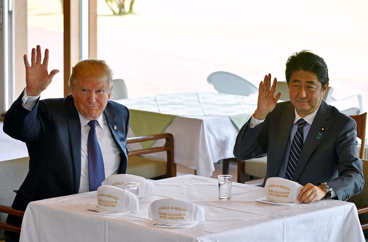 President Donald Trump and Japanese Prime Minister Shinzo Abe wave to reporters after they signed hats reading 'Donald and Shinzo, Make Alliance Even Greater'.