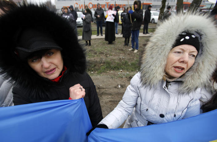"""Crimean Tatars shout slogans during the pro Ukraine rally in Simferopol, Crimea, Ukraine, Monday, March 10, 2014. Russian President Vladimir Putin on Sunday defended the separatist drive in the disputed Crimean Peninsula as in keeping with international law, but Ukraine's prime minister vowed not to relinquish """"a single centimeter"""" of his country's territory. The local parliament in Crimea has scheduled a referendum for next Sunday. (AP Photo/Darko Vojinovic)"""
