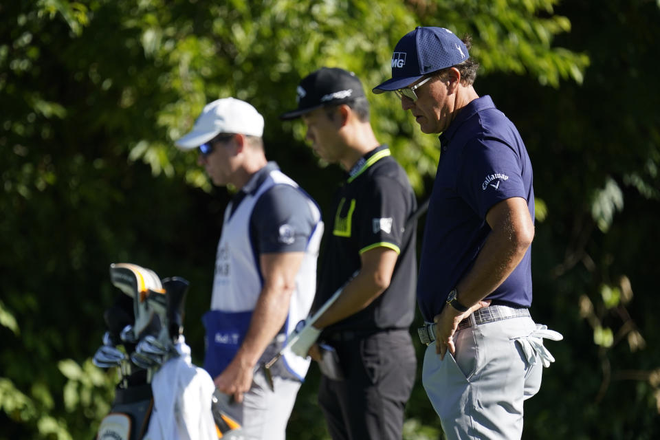 Phil Mickelson, right, Kevin Na, center, and their caddie observe a moment of silence on the 13th tee on Thursday. (AP Photo/David J. Phillip)
