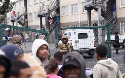 Crowds watch soldiers and police patrol Hanover Park town ship on Thursday - Credit: Brenton Geach/The Telegraph